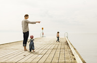 Mother showing something to baby girl while standing on pier at sea against sky - MASF04201