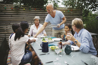 Man serving food to family at outdoor dining table - MASF04204