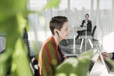 Mature businesswoman wearing earphones while sitting in office - MASF04207