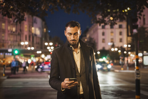 Man using smart phone on city street at night - MASF04213