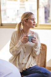 Blonde woman with cup of coffee looking out of the window - EBSF02391