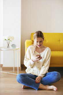 Blonde woman using smartphone at home - EBSF02406
