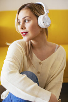 Blonde woman with headphones using smartphone at home - EBSF02409