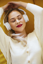 Blonde woman with headphones lying on sofa - EBSF02412