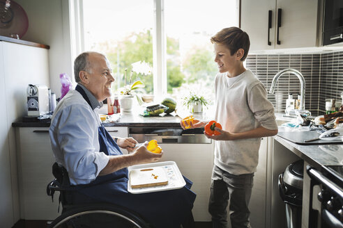Happy disabled father in wheelchair preparing food with son in kitchen - MASF04218
