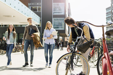 Happy friends walking by man with bicycle at campus - MASF04233