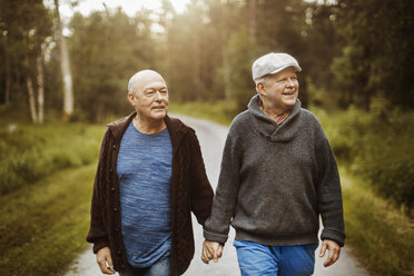 Happy gay couple looking away while walking on road amidst trees - MASF04236