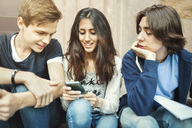 Happy girl using smart phone while sitting with male friends on steps - MASF04239