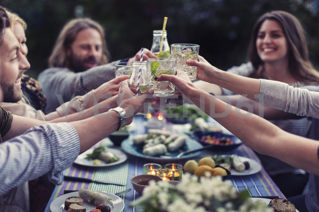 Happy friends toasting mojito glasses at dinner table in yard - MASF04248