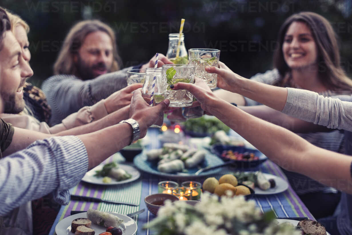 Happy friends toasting mojito glasses at dinner table in yard - MASF04248 - Maskot ./Westend61