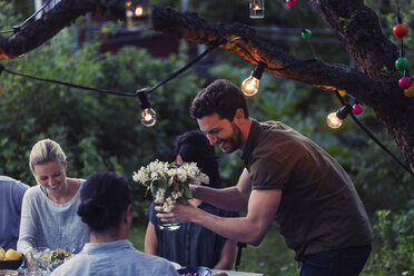 Happy man holding flower vase while enjoying dinner party with friends at yard - MASF04251