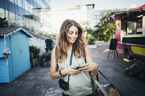 Happy female tourist using smart phone in city - MASF04257