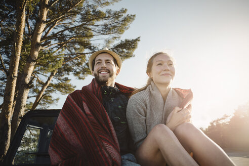 Happy wonderlust couple wrapped in blanket sitting on jeep against clear sky - MASF04266