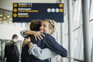 Happy businesswoman embracing male colleague at airport - MASF04269
