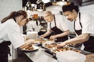 Kvinnlig sous chef och två manliga kockar förbereder maträtter - MASF04275