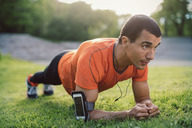 Man doing plank exercise on grassy field at park - MASF04299
