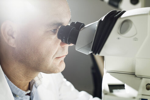 Male scientist using microscope at laboratory - MASF04311