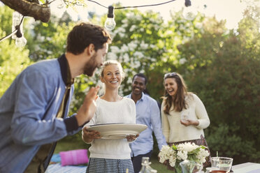 Happy young woman holding plate while enjoying summer party with friends in yard - MASF04314