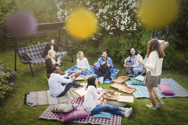 High angle view of friends having snacks during summer party at yard - MASF04317