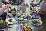 High angle view of friends sitting at dinner table in yard - MASF04320