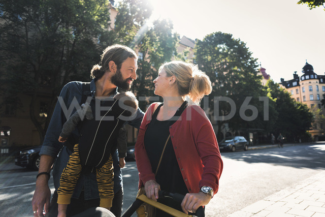 Loving mid adult parents with baby boy walking on sidewalk in city - MASF04323