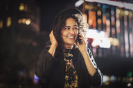 Happy young woman looking away while answering smart phone in city at night - MASF04335