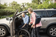 Disabled man disembarking from car on wheelchair held by woman - MASF04347