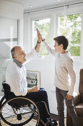 Disabled man in wheelchair giving high-five to son at home - MASF04350