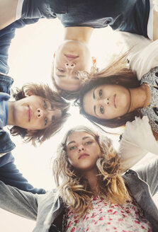 Directly below portrait of teenagers forming huddle against sky - MASF04365