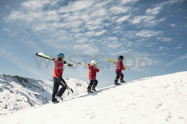 Father with two children carrying skis on snowy mountain against sky - MASF04395