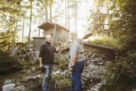 Gay men talking while holding gardening tools at field - MASF04404