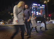 Full length of man using mobile phone on sidewalk in city at night - MASF04431