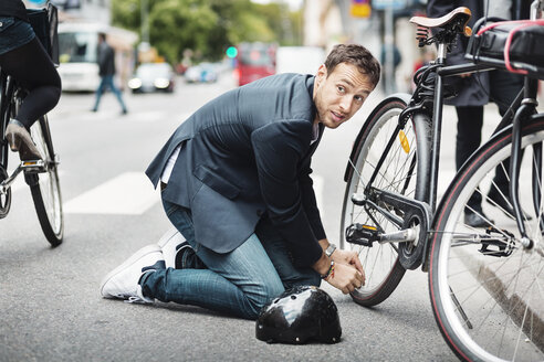 Businessman looking away while repairing bicycle on street - MASF04437