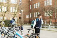 Boys talking on mobile phone by bicycle parking area outside school building - MASF04467