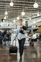 Businessman using smart phone while walking at airport - MASF04473