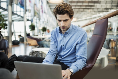 Businessman using laptop at airport lobby - MASF04476