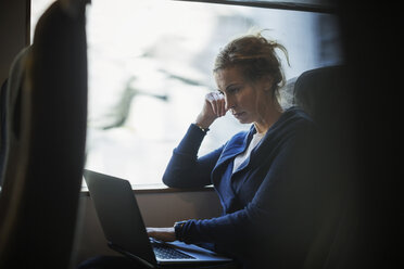Businesswoman using laptop in train - MASF04479