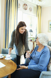 Young woman serving coffee to grandmother at home - MASF04494