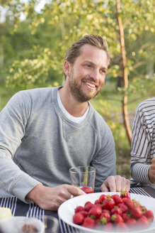 Smiling man having lunch with friend at picnic table - MASF04524