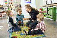 Teacher telling story to children in kindergarten - MASF04530