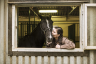 Young woman kissing horse in stable - MASF04542
