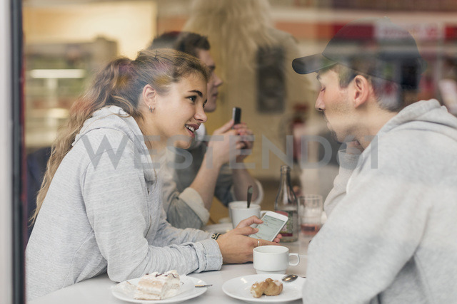 View of young couple talking while using smart phone in cafe through glass - MASF04581