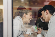View of happy young couple using smart phone in cafe through glass - MASF04584