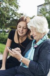 Young woman looking at grandmother using smart phone at park - MASF04587