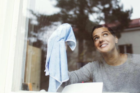 Woman cleaning glass of house window - MASF04593