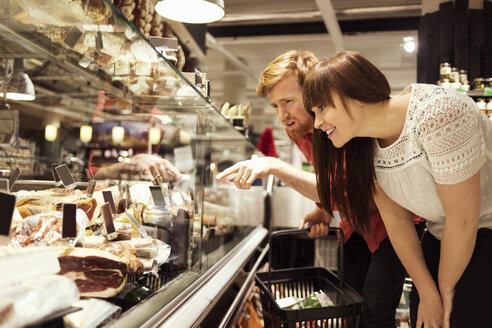 Young couple choosing fresh meat at supermarket - MASF04596