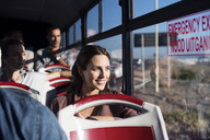 Tourists looking through window while traveling in tour bus - CAVF38522