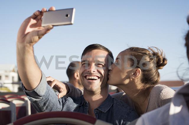 Happy man taking selfie while girlfriend kissing him in double-decker bus - CAVF38525
