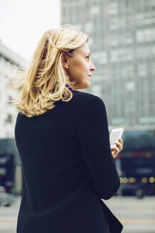 Rear view of businesswoman holding smart phone on city street - MASF04620