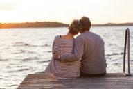 Rear view of affectionate couple sitting on pier against sea at sunset - MASF04647